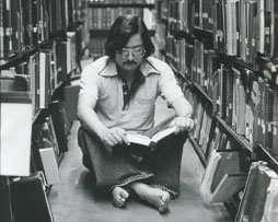Photo of a man sitting on the floor in a library